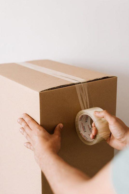 crop man sealing carton box with tape